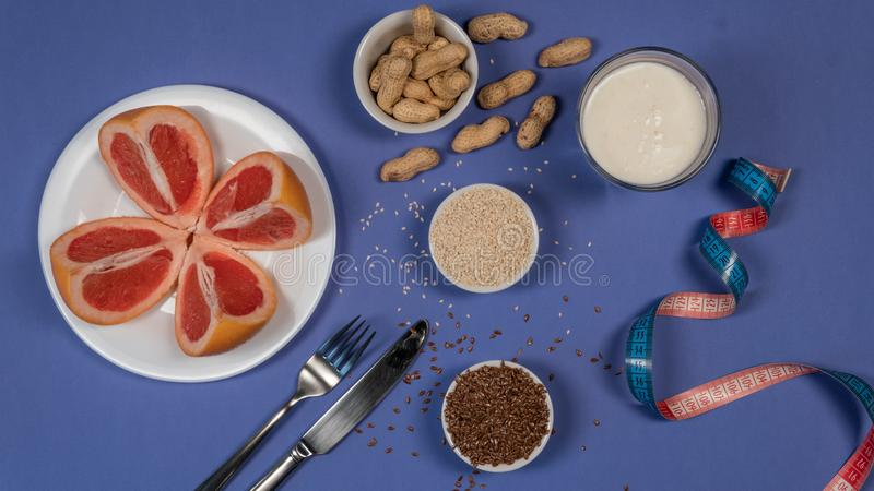 Concept diet - healthy food with grapefruit, peanut, sesame, flax seeds and measuring tape on blue background royalty free stock photos