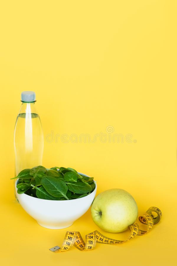Concept diet - healthy food. Water, spinach, apple and tape line on yellow background. Copy space. stock image