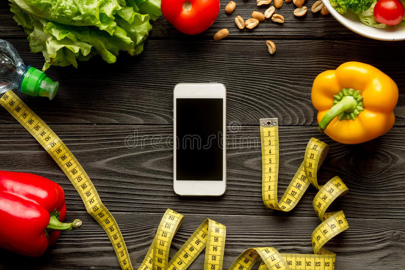 Concept diet and smartphone with vegetables mock up. On wooden background royalty free stock photography