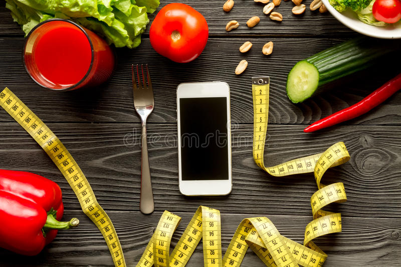 Concept diet and smartphone with vegetables mock up. On wooden background stock photos