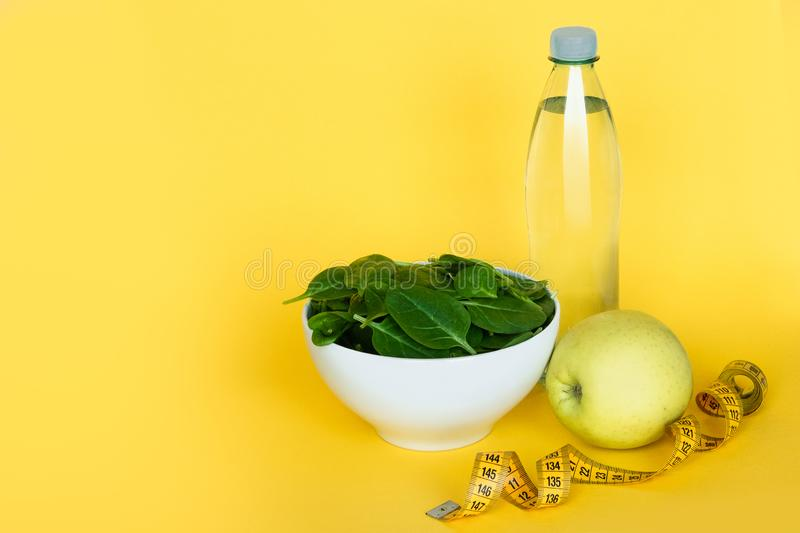 Concept diet. Water, spinach, apple and tape line on yellow background. Healthy food stock image