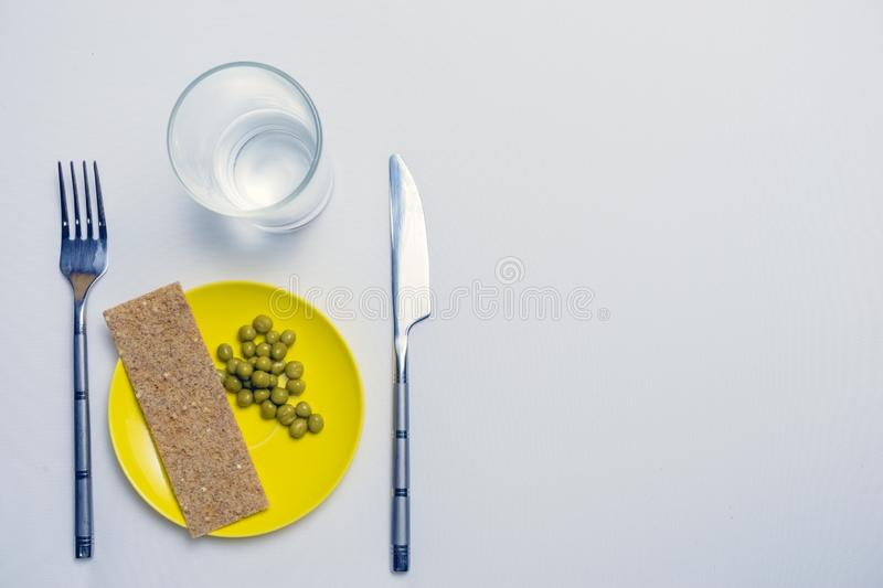 Concept of dietary restrictions, healthy lifestyle, diet, weight loss, fight obesity, healthy eating. peas and bread on a plate,. Knife, fork royalty free stock photo