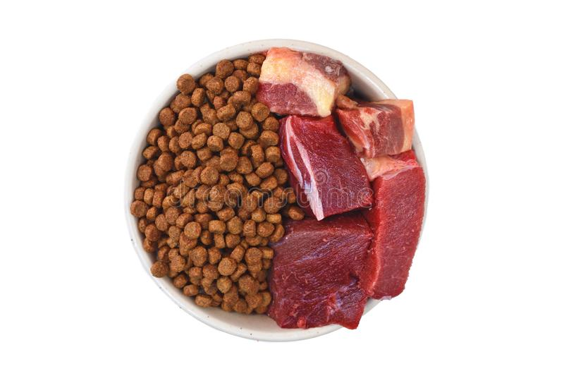 Concept of different dog or cat feeding methods with bowl half filled with dry food kibbles and half with chunk of raw meat on whi stock photos