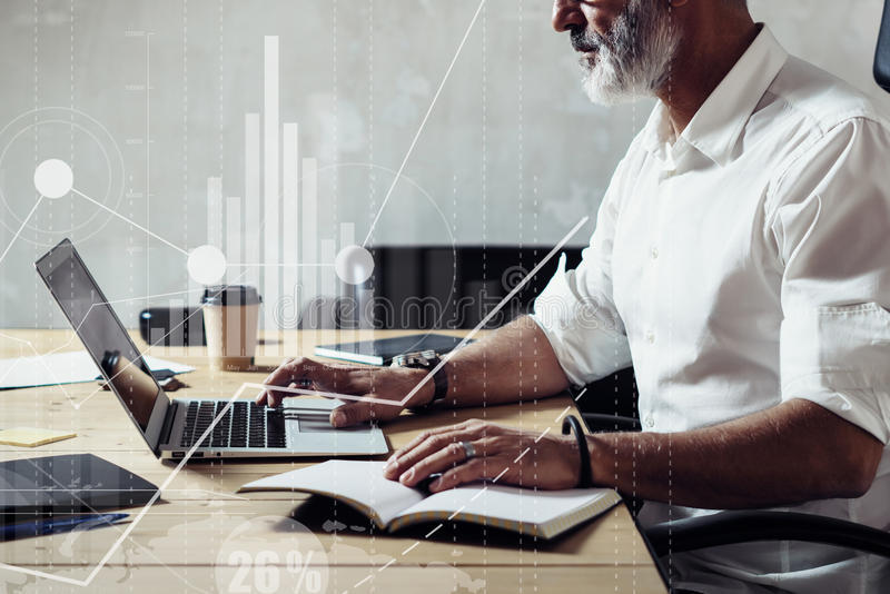 Concept of digital screen with global virtual icon,diagram, graph interfaces.Adult bearded businessman wearing a classic. Glasses and working at the wood table royalty free stock images