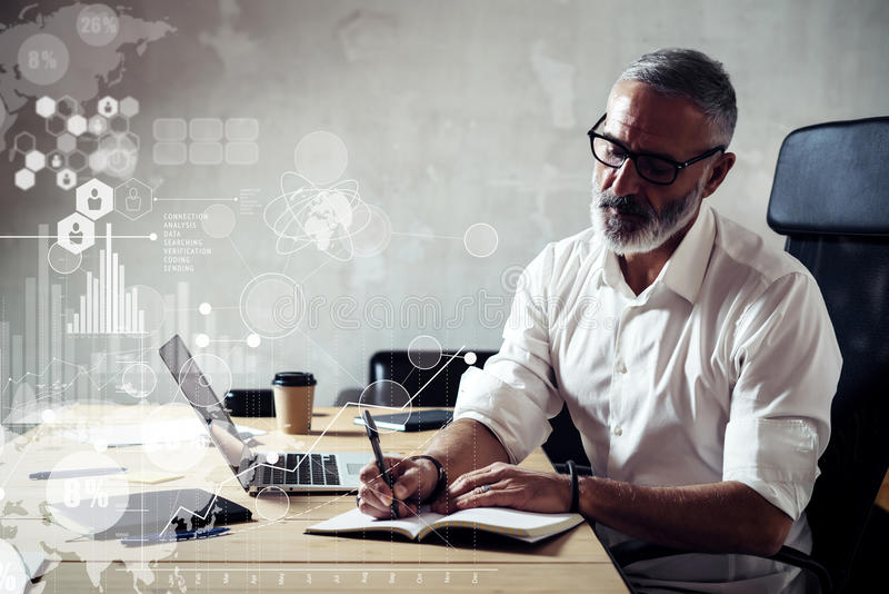 Concept of digital screen with global virtual icon,diagram, graph interfaces.Adult successful businessman wearing a. Classic glasses and working at the wood royalty free stock photo