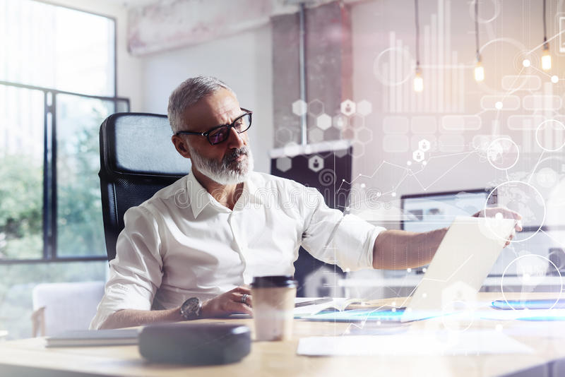 Concept of digital screen with virtual icon,diagram, graph and interfaces.Adult professional stock trader wearing a. Classic glasses working at the wood table royalty free stock image