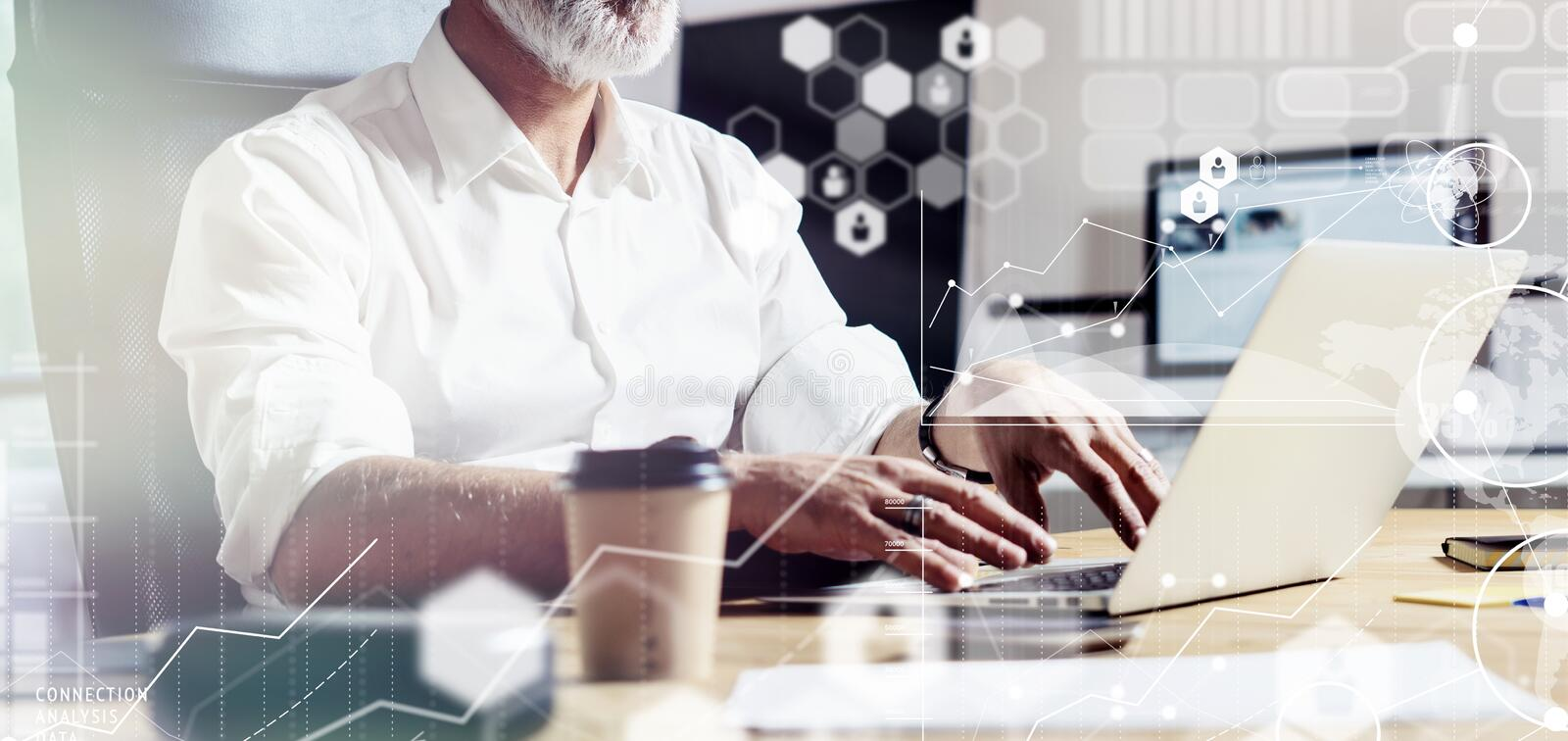 Concept of digital screen,virtual icon,diagram, graph and interfaces.Middle age account manager wearing a classic. Glasses, working at the wood table with royalty free stock photography