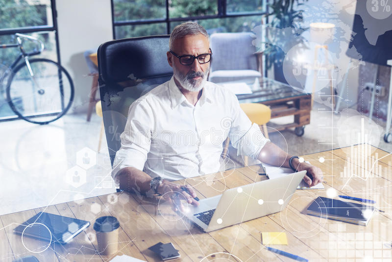 Concept of digital screen with virtual icon,diagram, graph and interfaces.Stylish bearded middle age man using laptop on. Workplace. Horizontal, blurred royalty free stock image