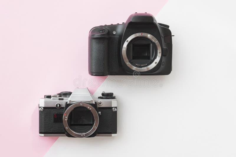 Concept - Digital vs. Analog SLR Camera on Pink Background stock photography