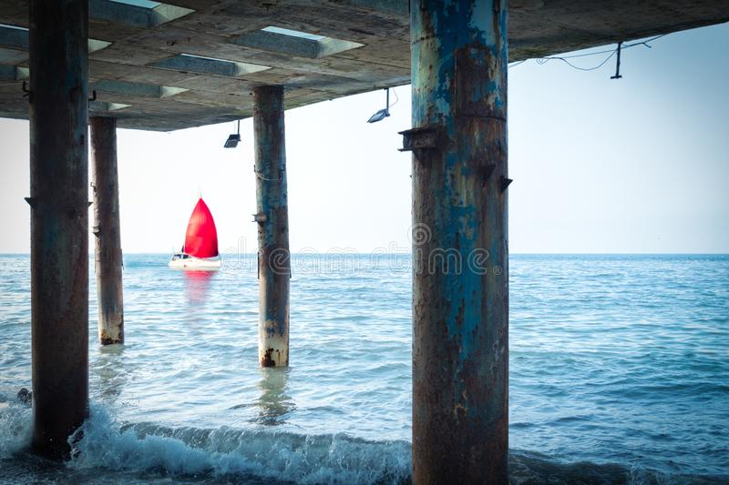 Concept of discovery, hope and travel - a sailboat with a red sail floats by the sea. View from the old pillars of the pier. Concept of discovery, hope and stock photo