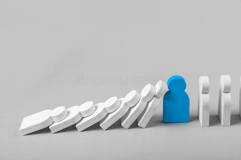 Concept of domino effect in business. The fall of the crumbling business is saved by special employee leader. The line of dominoes from the white figures of stock image