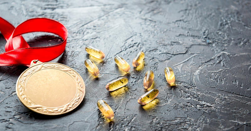 Concept of doping in sport - deprivation medals. Close up on dark background stock photos