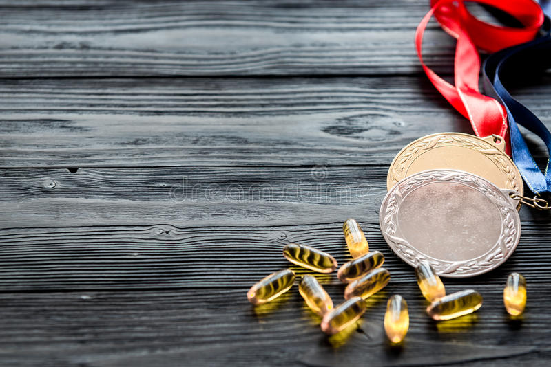 Concept of doping in sport - deprivation medals. Close up on dark wooden background stock photography