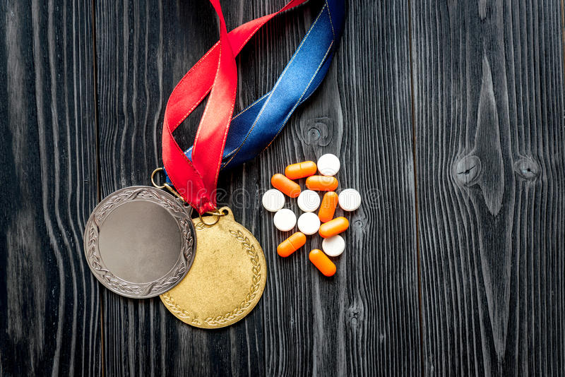 Concept of doping in sport - deprivation medals top view. On dark wooden background royalty free stock photos