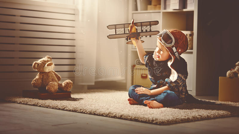Concept of dreams and travels. pilot aviator child with a toy a. Concept of children's dreams and travels. pilot aviator child with a toy airplane plays at home stock image
