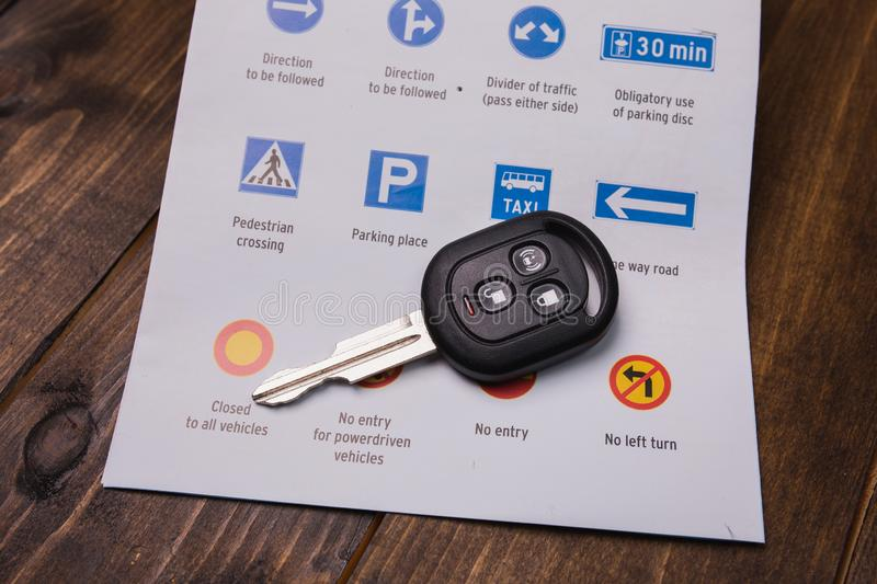 Concept - driving instruction. Closeup of road signs and car key. S on a wooden background stock photography