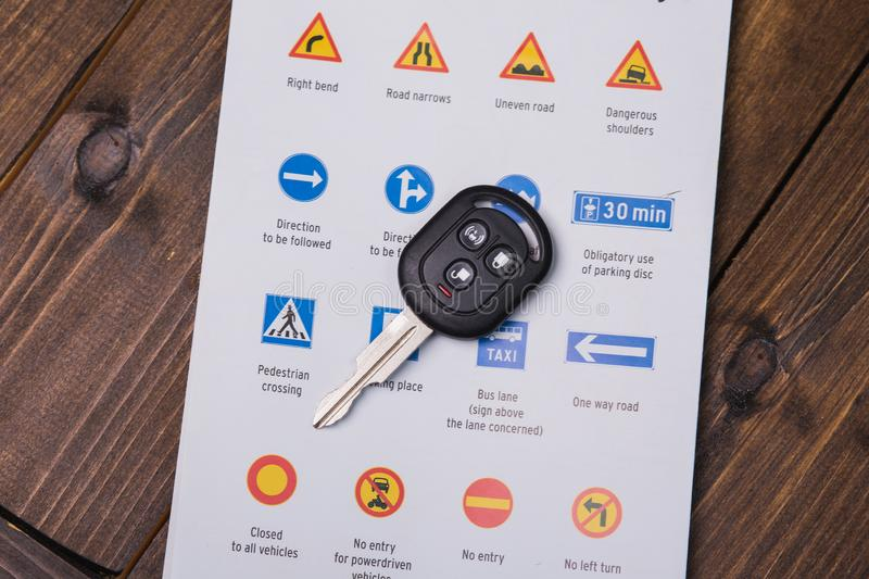 Concept - driving instruction. Closeup of road signs and car keys. On a wooden background stock photos