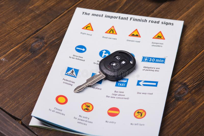 Concept - driving instruction. Closeup of road signs and car keys. On a wooden background stock images