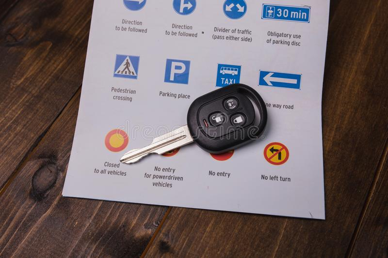 Concept - driving instruction. Closeup of road signs and car key. S on a wooden background stock photos