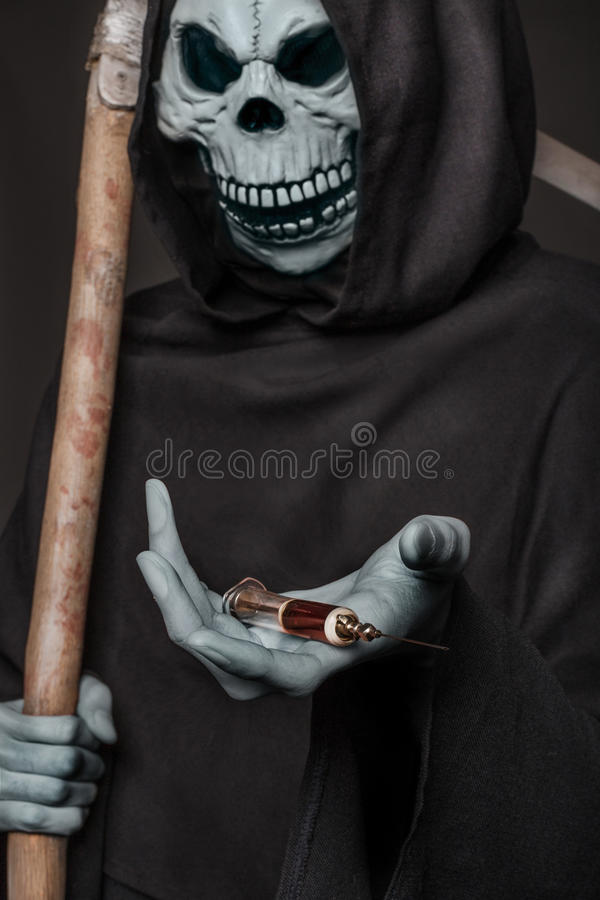 The concept: drugs kill. Angel of death holding syringe with heroin. Studio shot over black background stock image