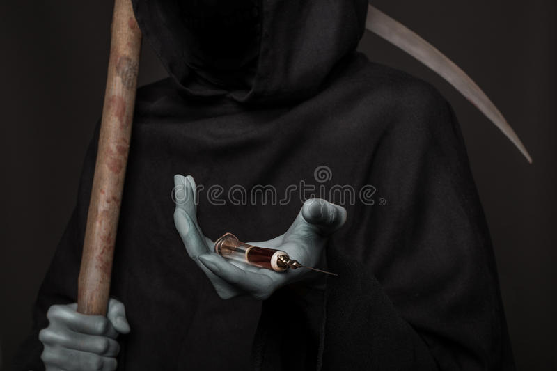 The concept: drugs kill. Angel of death holding syringe with heroin stock images