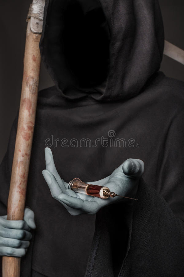 The concept: drugs kill. Grim reaper holding syringe with drugs. Studio shot over black background stock photo