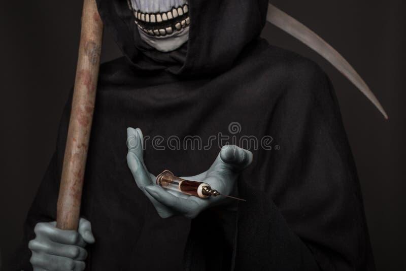 The concept: drugs kill. Grim reaper holding syringe with drugs. Studio shot over black background stock image