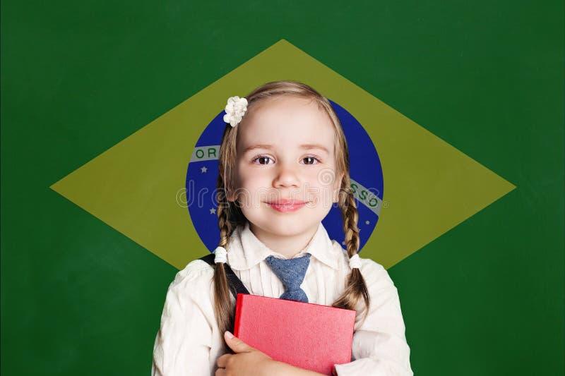 Concept du Brésil avec sourire peu d'étudiante avec le livre sur le drapeau du fond de la république fédérative du Brésil photographie stock