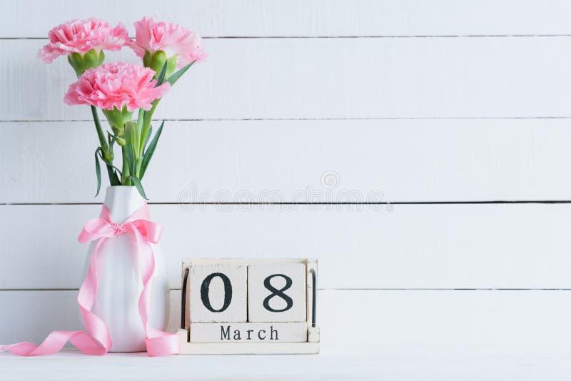 Concept du jour de la femme Fleur rose d'oeillet dans le vase avec le texte du 8 mars sur le calendrier de bloc en bois sur le fo photo stock