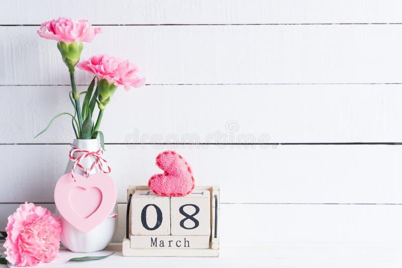 Concept du jour de la femme Fleur rose d'oeillet dans le vase et coeur rouge avec le texte du 8 mars sur le calendrier de bloc en images stock
