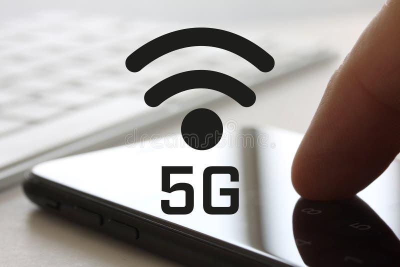 concept du réseau 5G avec le doigt touchant le smartphone avec l'écran et le keybord à l'arrière-plan Symbole sans fil d'Internet image libre de droits