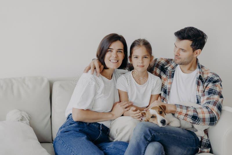 Concept du temps de famille Maman gaie, papa et petite fille embrassent tous ensemble, passent du temps libre dans le salon de le photo libre de droits