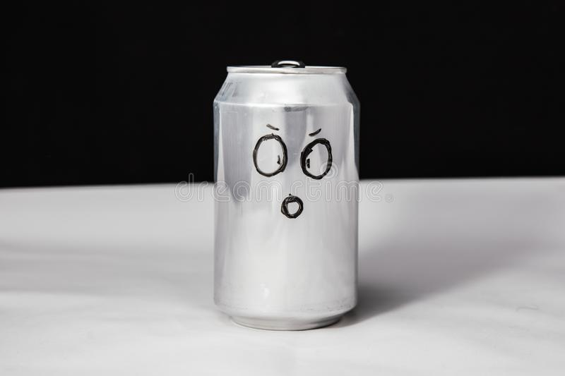 Concept of dumbfounded man. confused emoticon on aluminium 0.25l can, Emoji with surprised face. On black background.  stock image