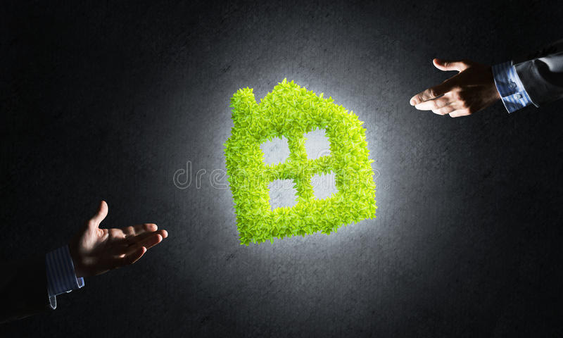 Concept of eco architecture presented by green house on dark background. Close of businessman hand and green house icon as symbol of save construction royalty free stock photography