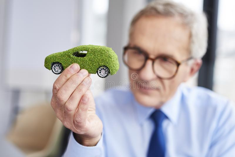 Concept of eco friendly car. Businessman holding a model of eco friendly car royalty free stock images