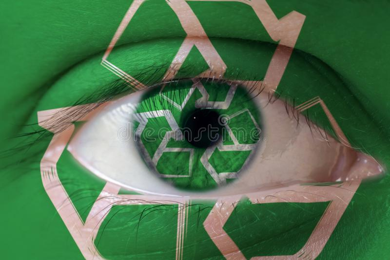 Concept of the ecologycal concern vision. Human face painted with recycle symbol on the face and the iris. The concept of the ecologycal concern vision stock illustration