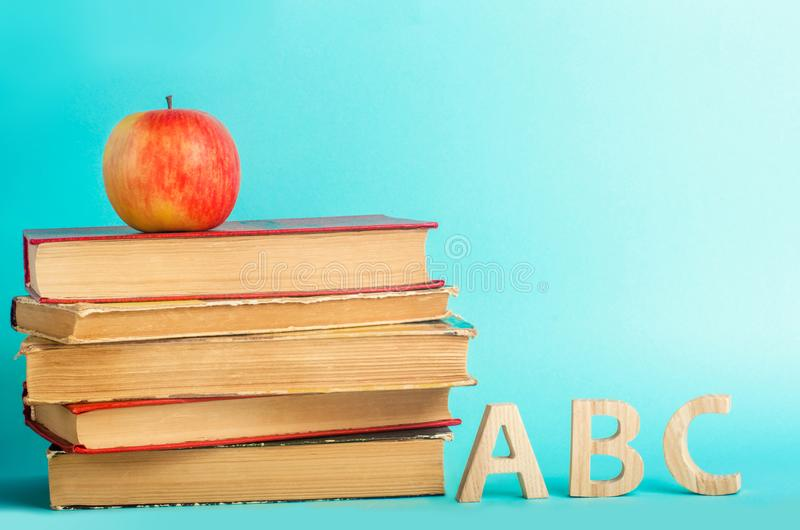 The concept of education. apple, books and alphabe, blue background, place for text, back to school, copy space stock photo