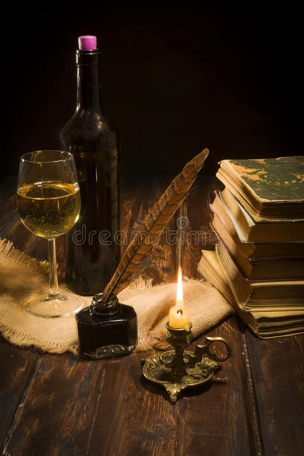 The concept of education and writing, an inkwell with a pen and. Concept of education and writing, an inkwell with a pen and a lit candle on the background of a royalty free stock images