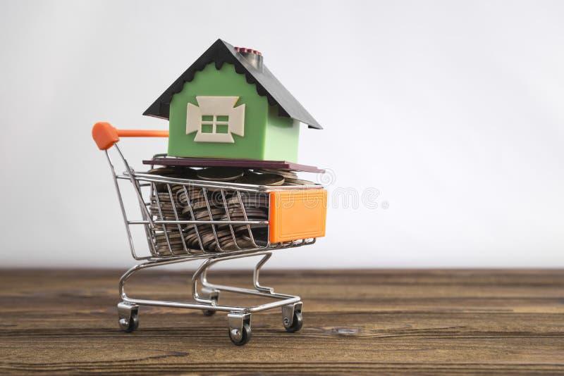 Concept een huis in een het winkelen karretje op een witte achtergrond Idee: kopend een huis, het huren, onroerende goederen verk royalty-vrije stock foto