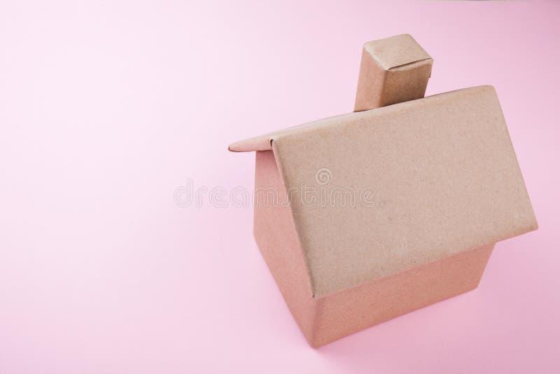 Concept, een huis van golfdiekarton wordt, op een roze achtergrond wordt geïsoleerd gemaakt die Plaats voor tekst royalty-vrije stock afbeelding