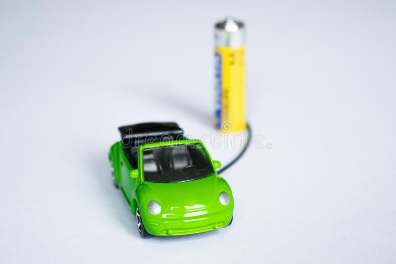 Concept of electric car. model car charge from battery. save planet. gas polution. Car model on white background royalty free stock images