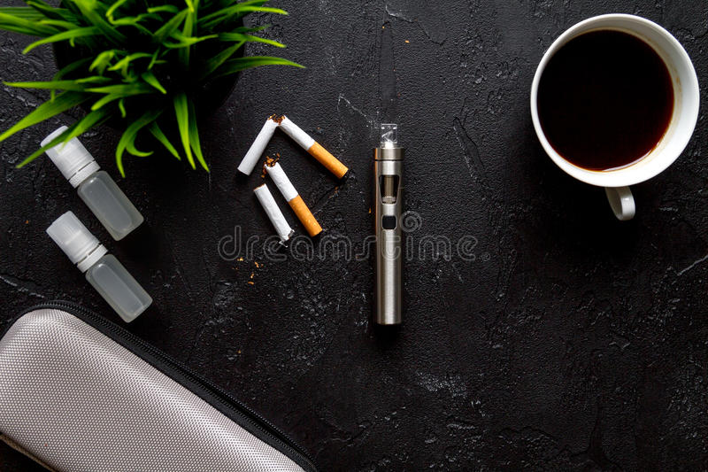 Concept of electronic cigarette on dark background top view.  stock photography