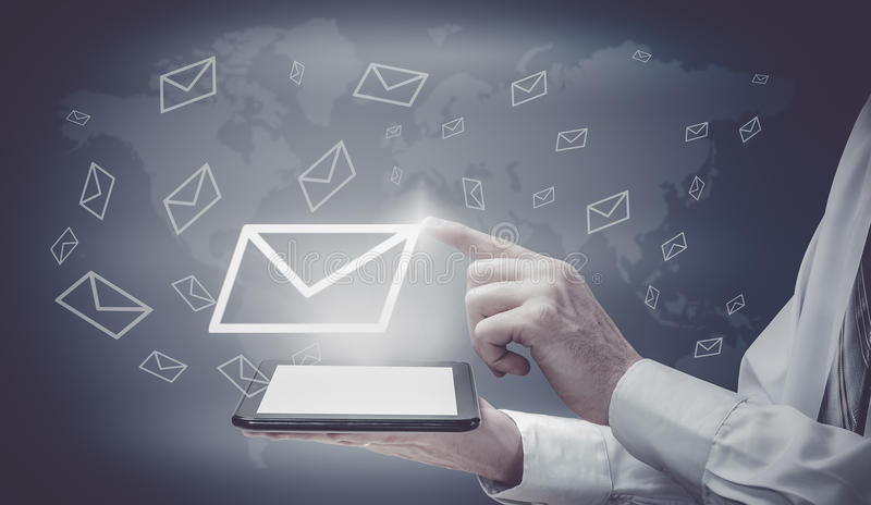 The concept of email marketing. Businessman makes sending emails from your tablet stock image