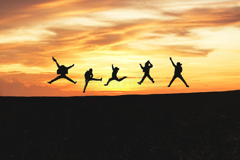 Concept of emotion. Silhouette of a happy group of people jumping at sunset in the mountain. With copy space stock images