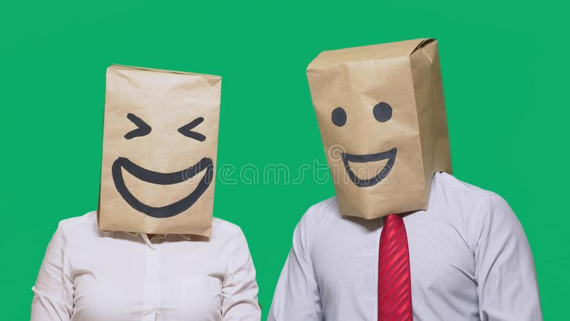 Concept of emotions, gestures. a couple of people with bags on their heads, with a painted emoticon, smile, joy, laugh. Concept of emotions, gestures. a couple stock images