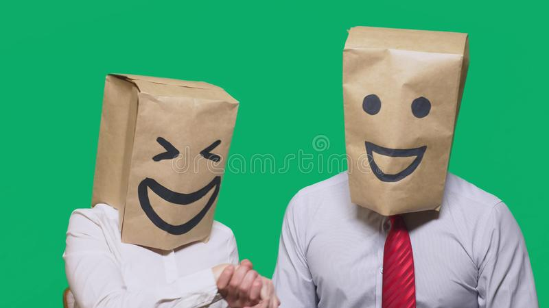 Concept of emotions, gestures. a couple of people with bags on their heads, with a painted emoticon, smile, joy, laugh. Concept of emotions, gestures. a couple stock image