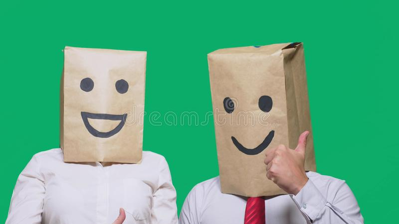 Concept of emotions, gestures. a couple of people with bags on their heads, with a painted emoticon, smile, joy, laugh. Concept of emotions, gestures. a couple stock photos
