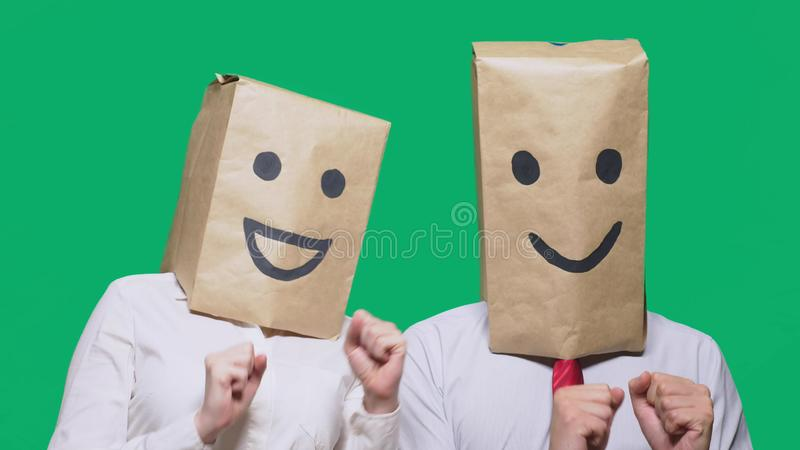 Concept of emotions, gestures. a couple of people with bags on their heads, with a painted emoticon, smile, joy, laugh. Concept of emotions, gestures. a couple stock photo