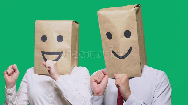 Concept of emotions, gestures. a couple of people with bags on their heads, with a painted emoticon, smile, joy, laugh. Concept of emotions, gestures. a couple royalty free stock photo