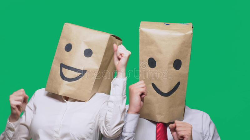 Concept of emotions, gestures. a couple of people with bags on their heads, with a painted emoticon, smile, joy, laugh. Concept of emotions, gestures. a couple royalty free stock photos